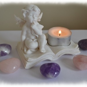 cherub sat on a book tealight holder